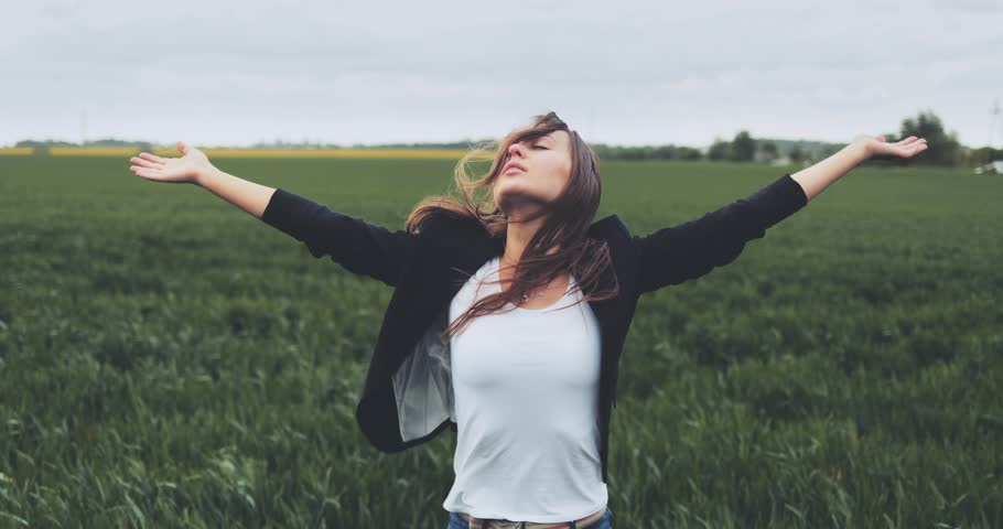 Portrait of Business Woman Standing on the Wind with Hands Up. SLOW MOTION 4K DCi. Businesswoman enjoying the wind, feeling free. Stormy weather, autumn, winter, spring. Royalty-Free Stock Footage #30491599