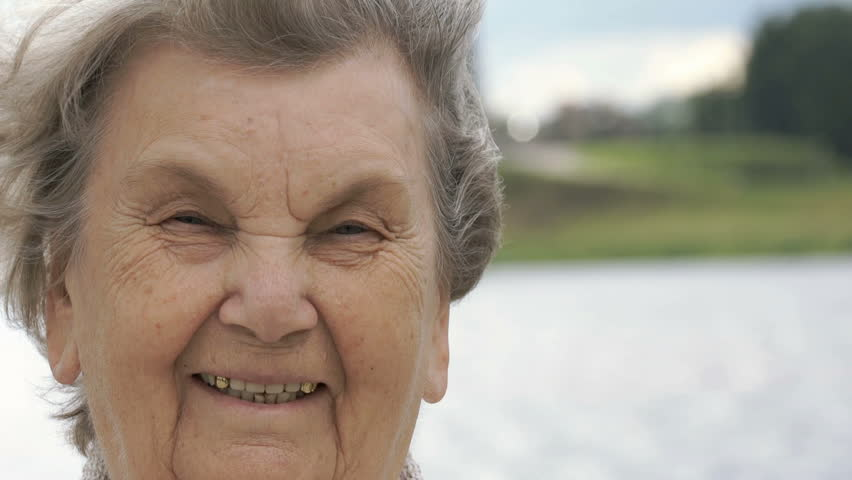 Portrait of smiling mature old woman with gray hair aged 80s on the background of river in summer. Slow Motion #30494398