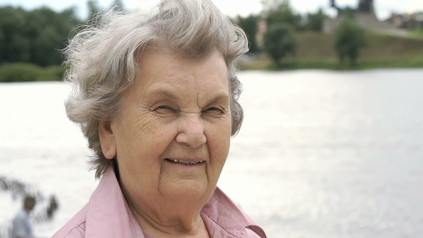 Portrait of smiling mature old woman with gray hair aged 80s on the background of river in summer. Slow Motion #30494410