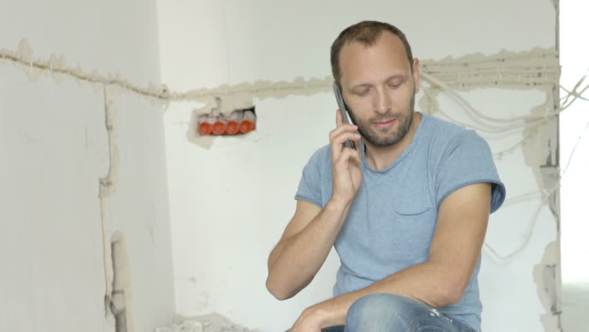 Man sitting on the blocks in his new apartment and talking on cellphone, steadycam shot    Shutterstock HD Video #30497554