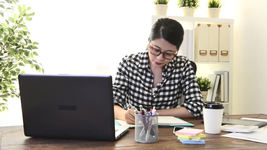 beautiful young lady business worker writing work schedule on personal notebook and thinking company proposal plan when she working at home.