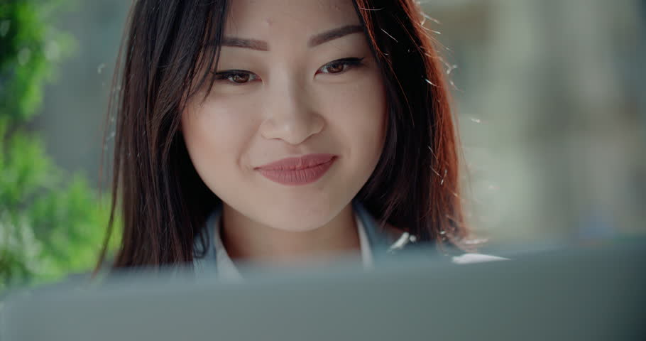 Close-up of a beautiful young successful Asian business girl with laptop in summer cafe | Shutterstock HD Video #30512614
