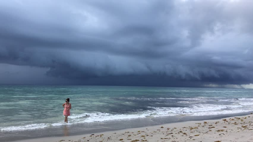 Hollywood, Florida - July 12,2017: Storm clouds approach  beach as people wait until the last moments to evacuate the beach before the rain begins.