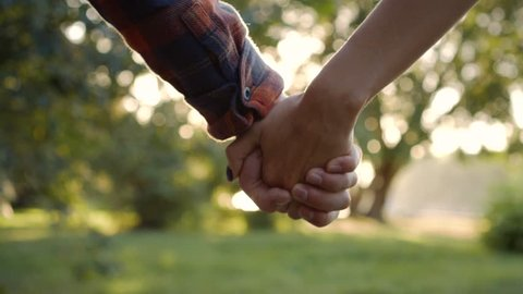 Young loving couple holding hands walking along the summer park.
