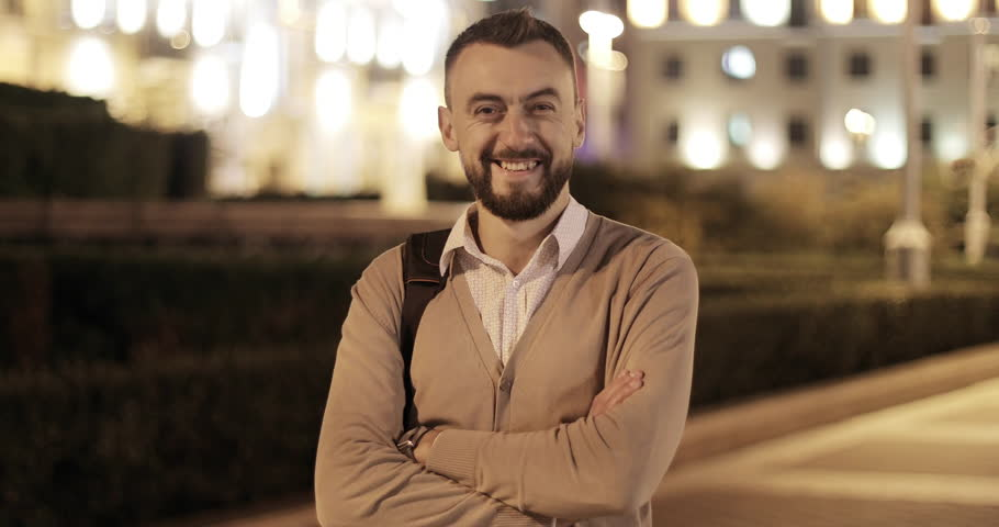 Middle aged attractive man with a beard on the background of a night city. The adult man looks at the camera and smiles. 4K footage. | Shutterstock HD Video #30544765