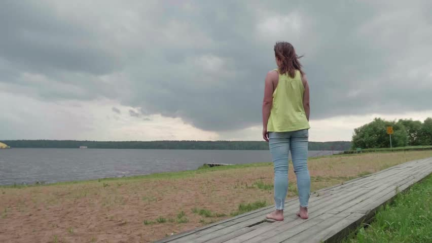 Slow motion of girl in yellow tank and blue jeans leaps for joy on bank of river on cloudy summer day