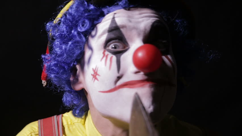 A clown makes face cutting movements with an axe.
