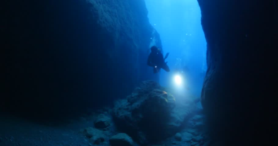 Cave diving underwater scuba divers exploring cave dive ocean scenery