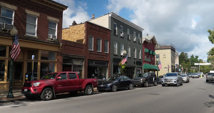 A daytime exterior establishing shot of a generic small town's Main Street shopping district storefronts and traffic.  Winter version available.