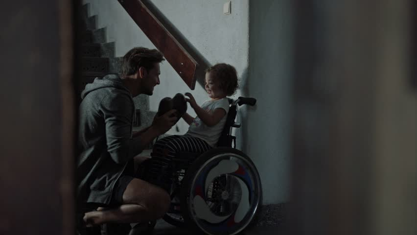 Young father taking care of his disabled child on a wheelchair