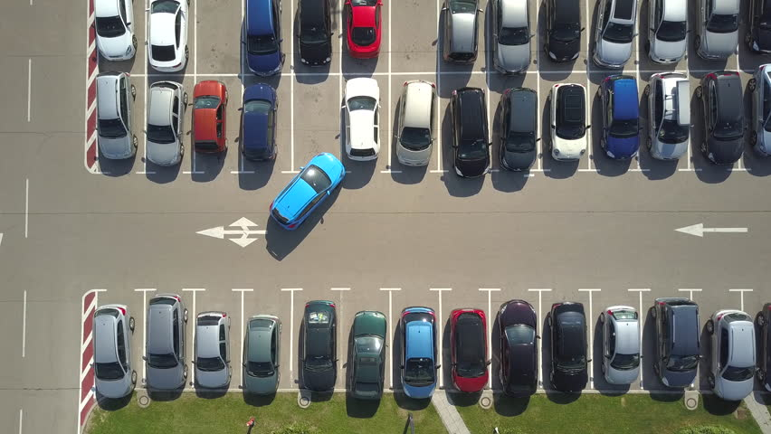 AERIAL TOP DOWN: Flying above bad driver incapable to park a car on parking space in big crowded parking lot. Driver having problems, unable to park a car in parking spot. Parking fail on parkspace