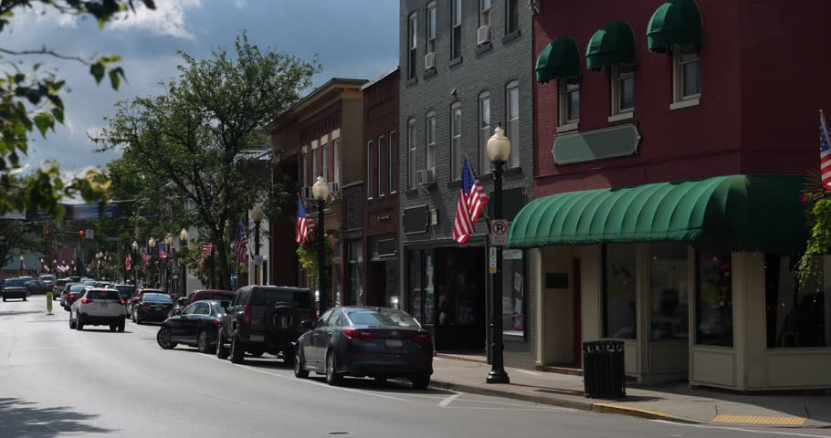 A morning exterior establishing shot of a generic American small town's Main Street shopping district storefronts and traffic. 	Winter version available.