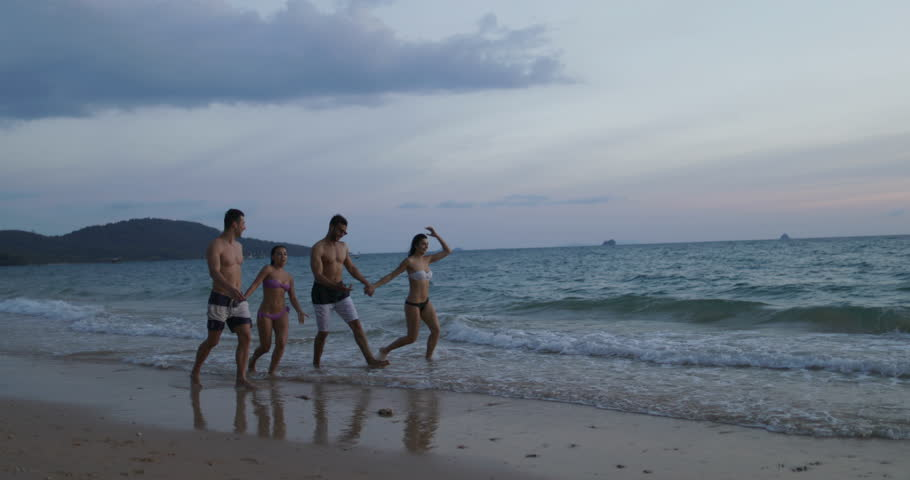 Group Of People Walking On Beach At Sunset, Two Mix Race Couple Communication During Summer Vacation Slow Motion 60 #30585856