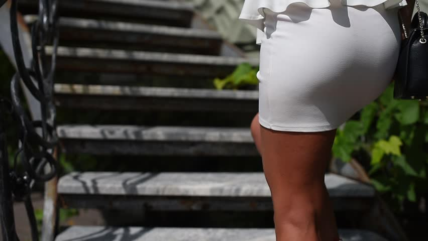 Beautiful female feet, in expensive red shoes climb the stairs, smooth image, a warm sunny day