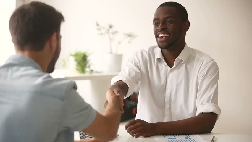 Happy satisfied diverse businessmen making commitment handshaking after successful negotiations, african black entrepreneur shaking hand of new caucasian white partner closing good business deal