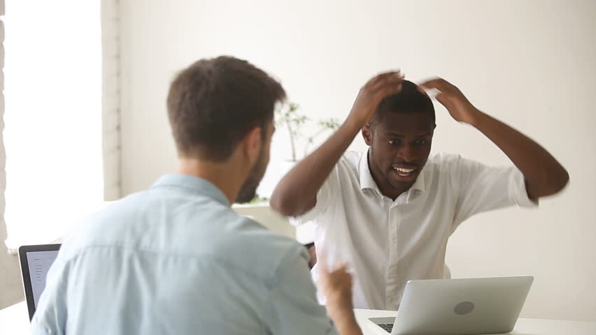 African american businessman excited about great unbelievable win online, raising hands looks at laptop, celebrating business success with partner in office, great news, successful deal, breakthrough