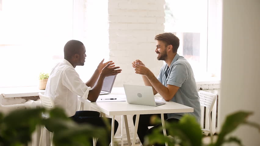 African american and caucasian businessmen talking in loft office, diverse colleagues joking laughing in friendly easygoing coworking atmosphere, good relations at workplace, making friends at work