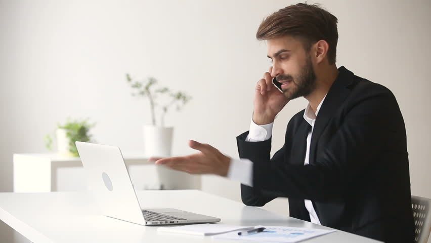 Angry businessman arguing shouting while talking on phone looking at laptop sitting at office desk, dissatisfied client explaining computer problem to customer support, complaining about bad service