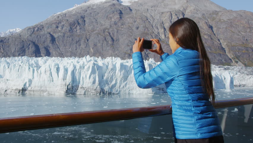 Alaska cruise ship passenger photographing glacier in Glacier Bay National Park, USA. Woman tourist taking photo picture using mobile cell smart phone on travel vacation. Margerie Glacier.