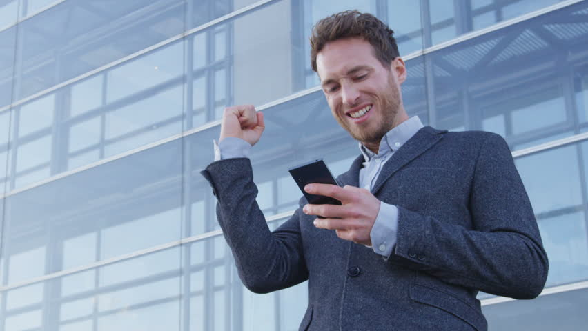 Success and achievement - happy businessman cheering celebrating looking at cell phone. Young urban professional successful business man receiving good news in business. Smartphone app concept