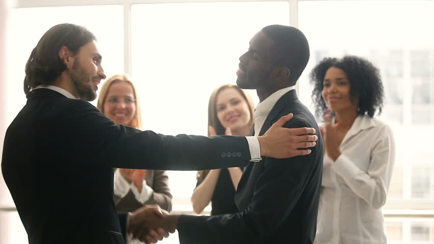Boss promoting rewarding african american male worker, appreciating for good job, businessmen wearing suit congratulating shaking hands with applauding staff standing in office, employee recognition