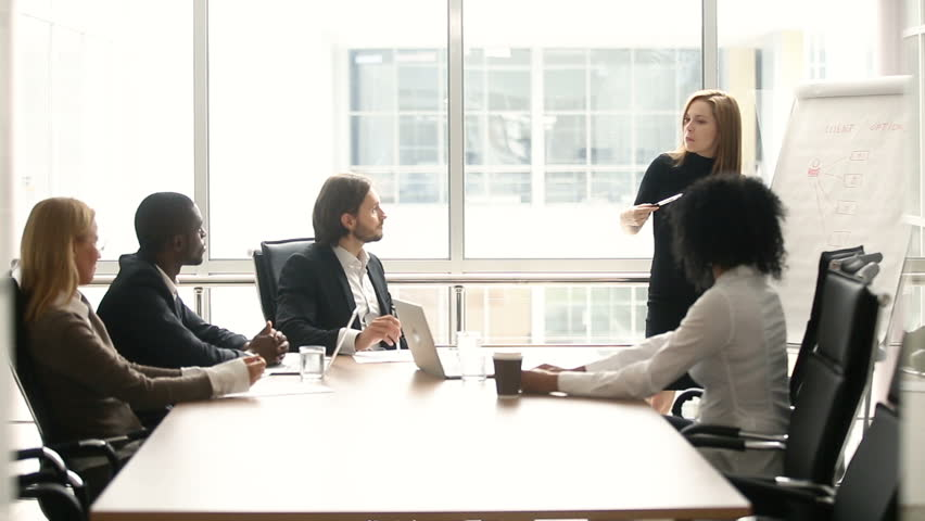 Businesswoman giving presentation to multi-ethnic colleagues at meeting, company manager presenting new plan for project team in boardroom, office worker explaining business strategy with flipchart | Shutterstock HD Video #30610984