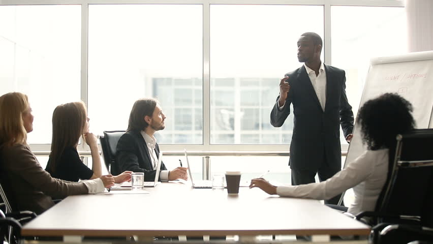 African american coach gives corporate presentation for businesspeople in office, dark skinned businessman presents new business plan on whiteboard, speaking to clients listening speaker at meeting Royalty-Free Stock Footage #30610993