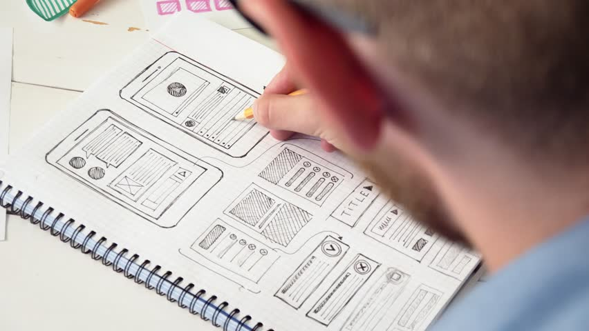 Young UX designer sketching prototype of a new app in his notebook Royalty-Free Stock Footage #30614758