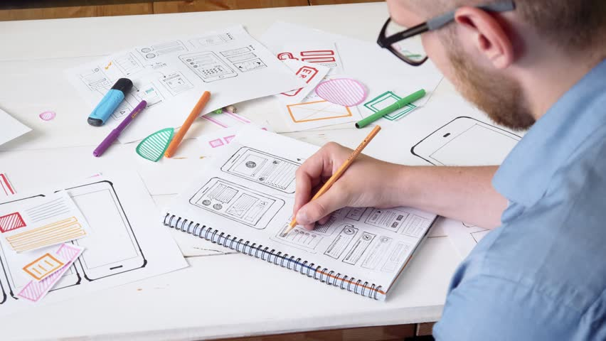 Young UX designer sketching prototype of a new app in his notebook Royalty-Free Stock Footage #30614794