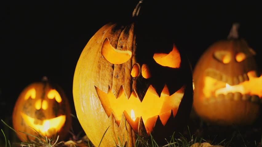 Halloween pumpkin head jack o' lantern with burning candles over black background. Halloween holidays art design, celebration | Shutterstock HD Video #30616306