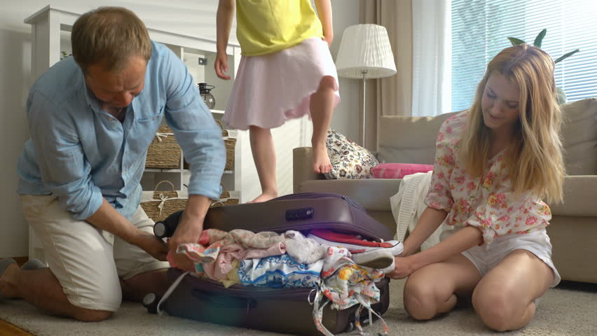 A Young Family with Child Trying to Close the Chock-full Suitcase