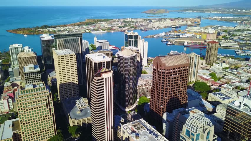 Aerial View of Buildings in Downtown Honolulu, Oahu Hawaii.  Blue sky, pacific ocean, harbor in background.  Tall buildings near Waikiki.  Footage in 4K at Hawaii's Capital City.  Skyline Scenic View.