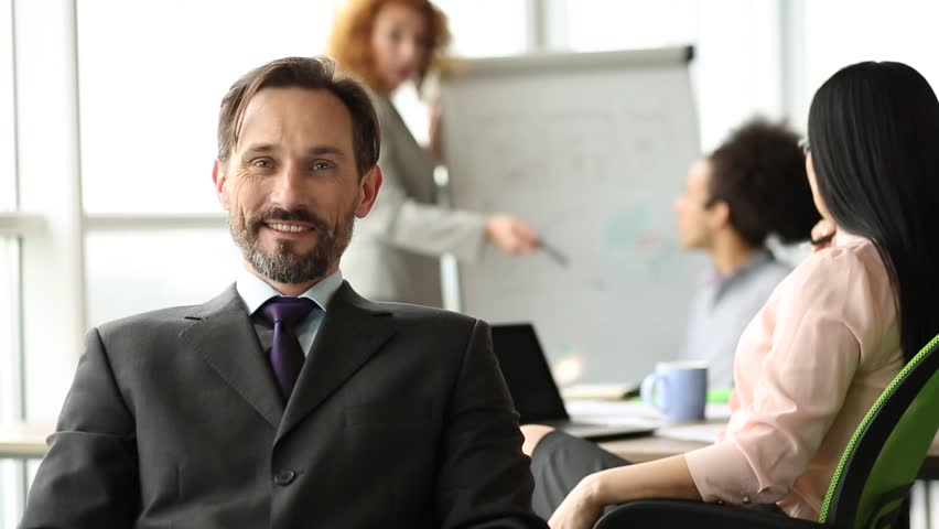 Smiling businessman sitting in the office with his back to coworkers. Happy director on meeting of team of coworkers. | Shutterstock HD Video #30656725