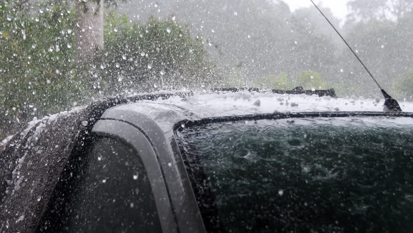 Heavy rain and hail falling on roof of car during violent storm