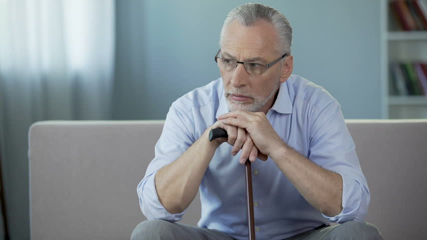 Ill man in his 50s sitting on couch, putting hands on walking stick. Depression | Shutterstock HD Video #30659632