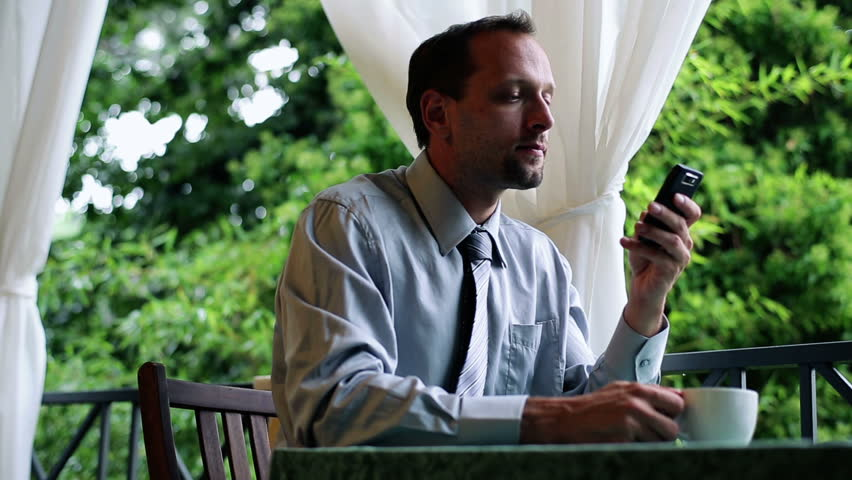 Young businessman with cellphone drinking coffee on his balcony  | Shutterstock HD Video #3067072