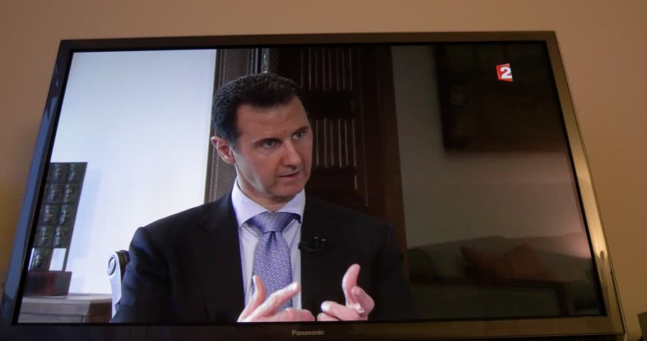 PARIS, FRANCE - APR 20, 2015: Interview of Syrian President Bashar al-Assad to David Pujadas from France TV on TV screen in living room on evening news special edition | Shutterstock HD Video #30675250