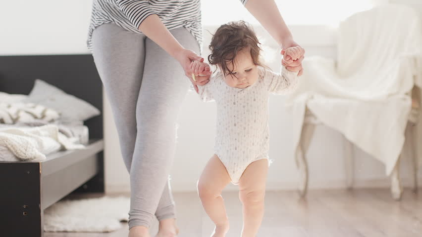 Baby taking first steps with mother help #30679645