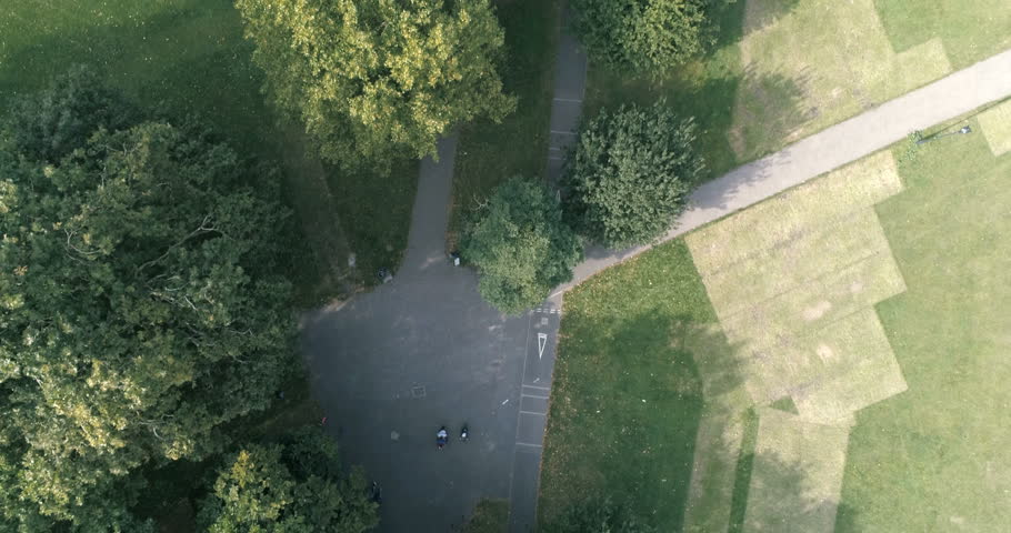 Aerial top down dolly view of a tree lined cycling path in a park in South London #30698476