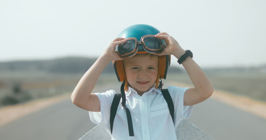CU Little boy putting on vintage googles and helmet, pretending to be a pilot. 4K UHD RAW edited footage