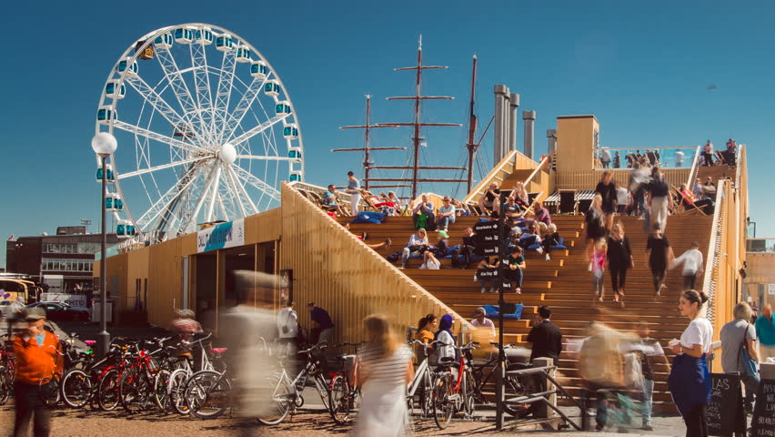 HELSINKI, FINLAND - JULY 21, 2017: people passing by SkyWheel and entrance to Allas Sea Pool with restaurant, a popular attraction in the city center, time lapse