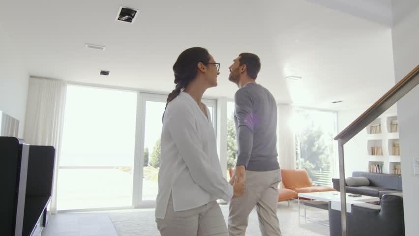 Happy Young Couple Enters Their Newly Purchased Home, They're Full of Wonderment. House is Bright, Has Floor to Ceiling Windows and Seaside View. Shot on RED EPIC-W 8K Helium Cinema Camera.