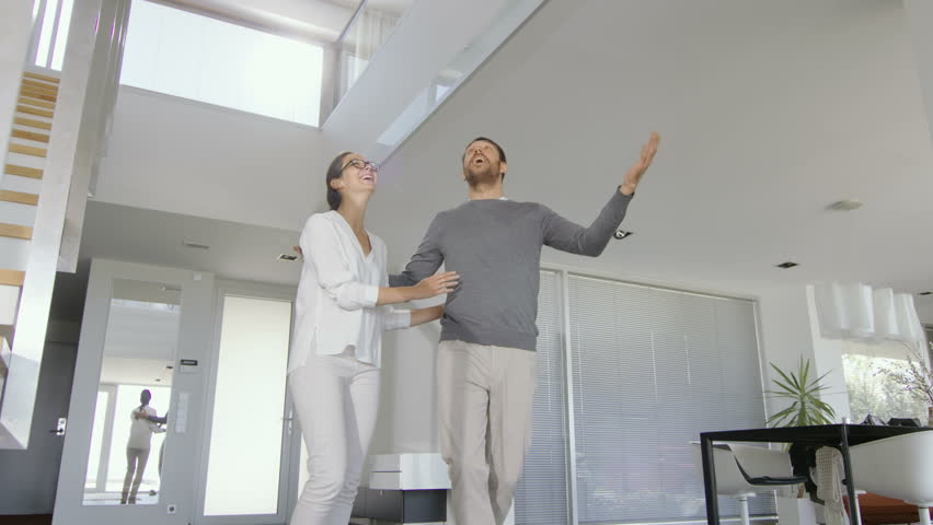 Beautiful Young Couple Enters Their Newly Purchased House, They're Very Happy and Their Home is Bright, Spacious and Modern. Shot on RED EPIC-W 8K Helium Cinema Camera. Royalty-Free Stock Footage #30700840