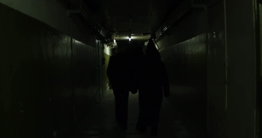 A frightening man in a mask in a long hallway 4k | Shutterstock HD Video #30707281