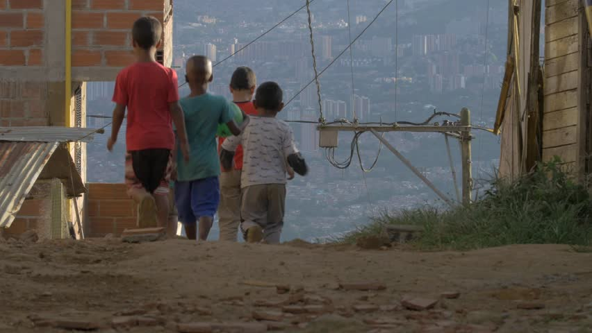 MEDELLIN, COLOMBIA - JULY 2017: POOR KIDS WALK DOWN AN ALLEY (BRINGING A FOOTBALL) 4K