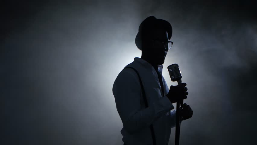 Man african american singer in the smoke and white light sings into a microphone and dance. Black background. Silhouette