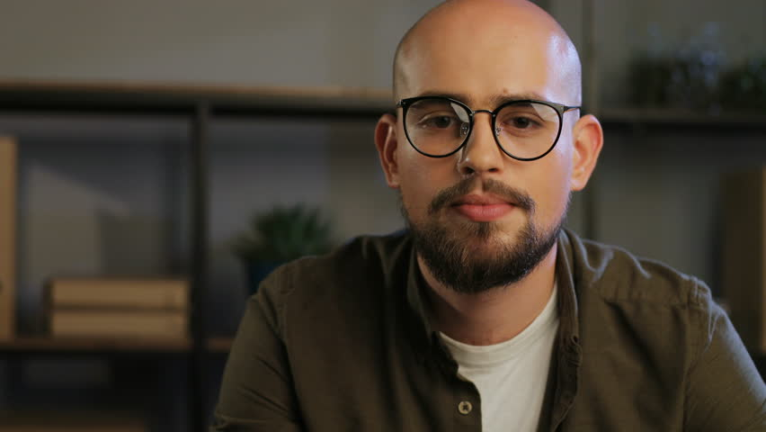 Portrait of handsome business man with beard in the glasses smiling at the camera and smiling on the office background. | Shutterstock HD Video #30735496