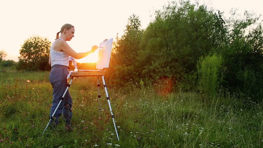 A woman artist with a brush and polytray in her hands draws on canvas against the backdrop of nature. The artist draws on the easel. Artist at work