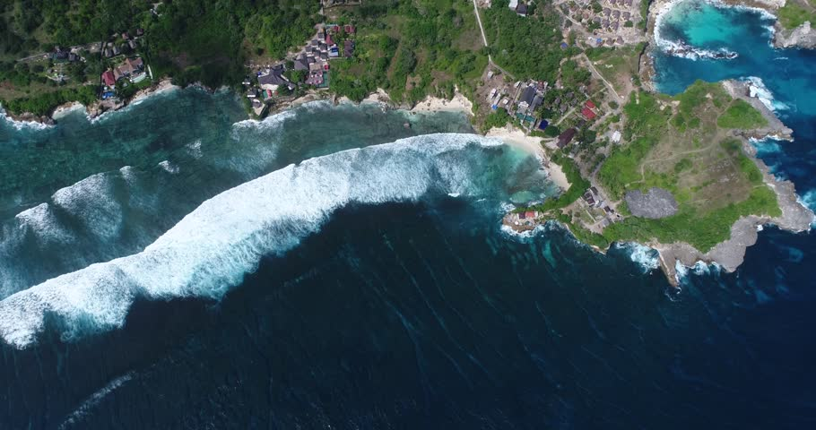 Drone footage of waves crashing on the shallow reef of the west part of Nusa Ceningan. The camera is facing down at birdview angle high over the waves and is going along the coast.   Shutterstock HD Video #30766306