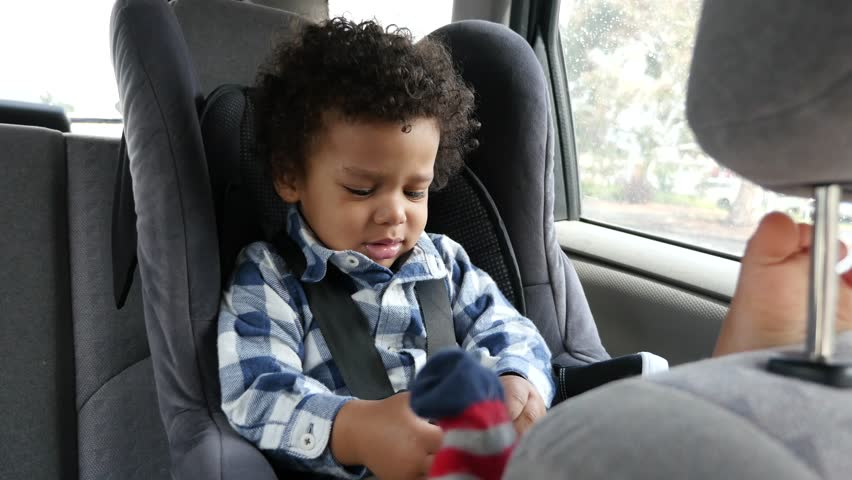 Unhappy child, crying  child pull of his socks in a car | Shutterstock HD Video #30771568